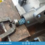 Opening the oil pump spring cap to insert a washer under the spring.